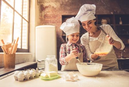 Het leuke meisje en haar mooie moeder in chef-kokhoeden glimlachen terwijl thuis het bakken