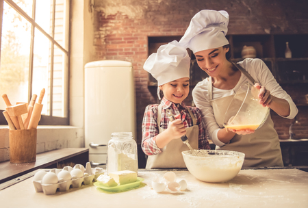 Cute little girl and her beautiful mother in chef hats are smiling while baking at home