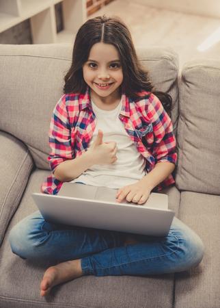 Het leuke meisje in vrijetijdskleding gebruikt laptop, toont Ok teken en glimlacht terwijl thuis het zitten op bank