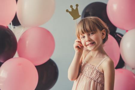 Cute little princess in dress is holding a crown, looking at camera and smiling, on gray background with colorful balloons Standard-Bild