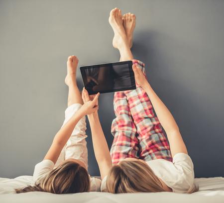 De mooie vrouw en haar leuke kleine dochter gebruiken een digitale tablet terwijl het liggen op bed met hun opgeheven benen