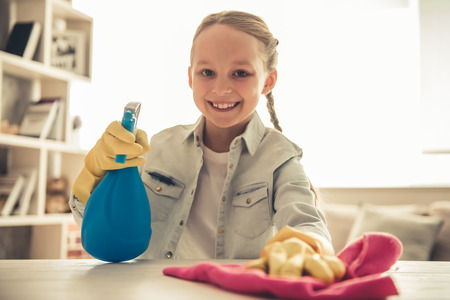 Pretty little girl in protective gloves is looking at camera and smiling while cleaning her house Stock Photo