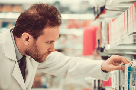 Handsome pharmacist is searching for medicine while working in pharmacy Stok Fotoğraf
