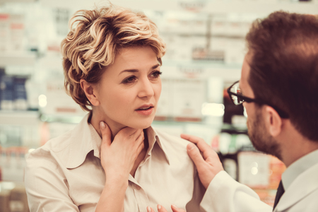 Handsome pharmacist is suggesting a medicine to a beautiful female client at the pharmacy. Woman is having a sore throat