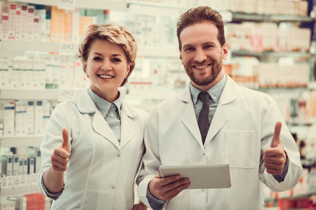 skill: Beautiful pharmacists are showing thumbs, looking at camera and smiling while working in pharmacy