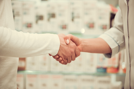 Cropped image of pharmacist shaking hands with a client at the pharmacy