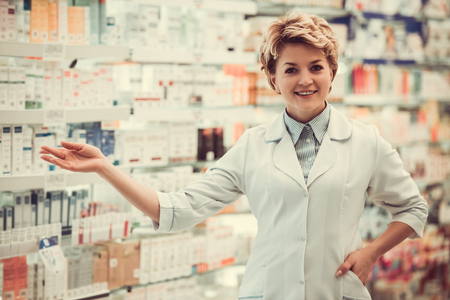 suggest: Beautiful pharmacist is showing rows of medicine, looking at camera and smiling while standing in pharmacy