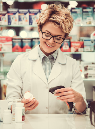 skill: Beautiful pharmacist is selling medicine and smiling while working at the cash desk in pharmacy