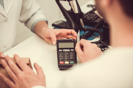 skill: Cropped image of pharmacist giving a purchase to a client and talking a credit card while working at the cash desk in pharmacy Stock Photo