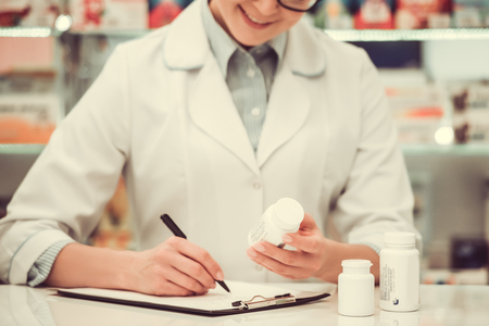 skill: Beautiful pharmacist is taking notes and smiling while working at the cash desk in pharmacy