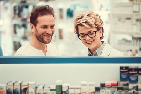 Beautiful pharmacist is suggesting drug to a client at the pharmacy and smiling