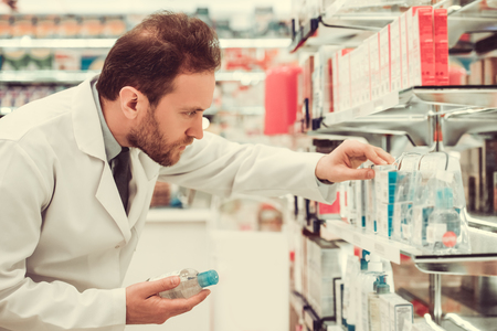 suggest: Handsome pharmacist is searching for medicine while working in pharmacy Stock Photo