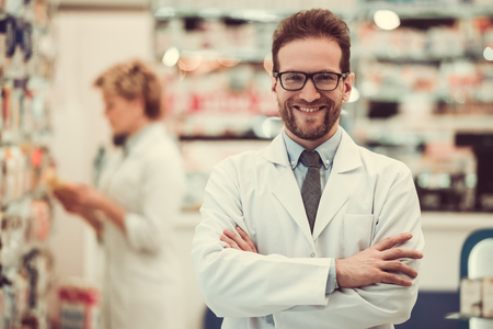 skill: Beautiful pharmacists working in pharmacy. Man is looking at camera and smiling