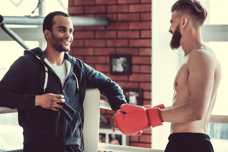 Handsome young muscular boxers are talking and smiling while training at the fight club Stock Photo