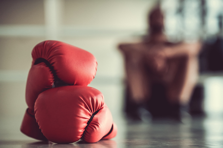 Red boxing gloves in the foreground, boxer is sitting on the boxing ring in the background