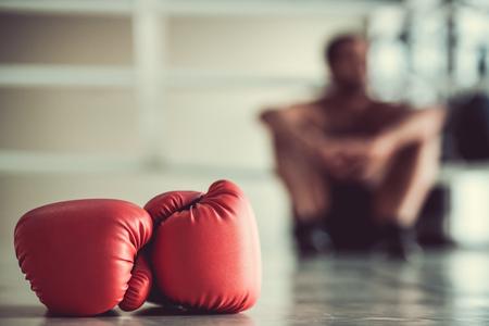 Rode bokshandschoenen op de voorgrond, bokser zit op de boksring op de achtergrond