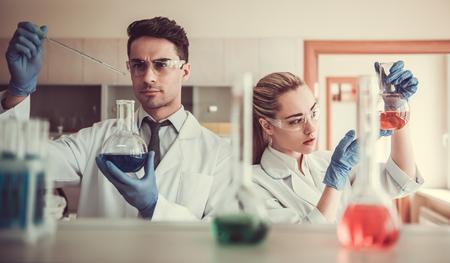 Aantrekkelijke artsen in handschoenen en veiligheidsbrillen werken met reageerbuizen in het laboratorium