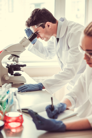 Attractive young medical doctors are working with test tubes and microscope at the lab