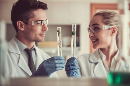 Attractive medical doctors in gloves and protective glasses are smiling while working with test tubes at the lab