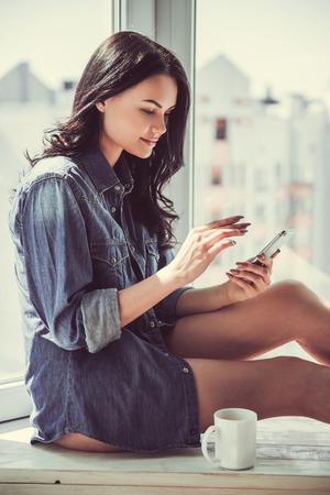 ジャン シャツの美しい若い女性のスマート フォンを使用し、窓枠自宅に座って笑顔