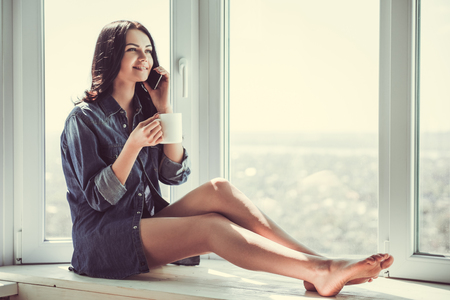 Beautiful young woman in jean shirt is talking on the mobile phone, drinking tea and smiling while sitting on the window-sill at home