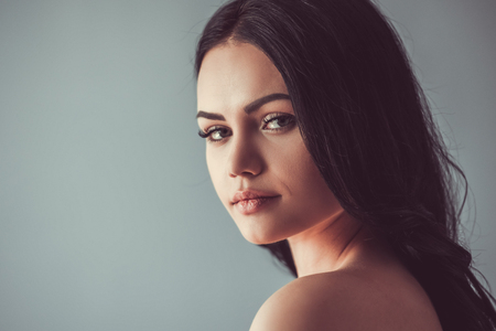 Portrait of beautiful young brunette with bare shoulders looking at camera, on gray background Фото со стока