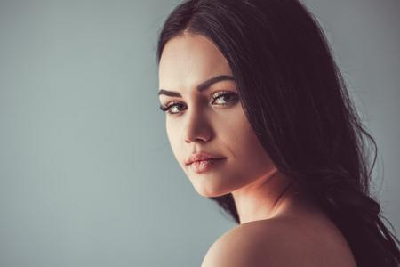 Portret van mooie jonge brunette met blote schouders naar camera kijken, op grijze achtergrond