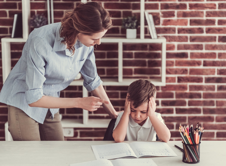 argues: Beautiful woman is scolding her cute little son while he is doing homework