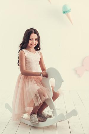 Het mooie schoolmeisje in kleding zit op hobbelpaard, bekijkt camera en glimlacht, op lichtblauwe en roze achtergrond Stockfoto