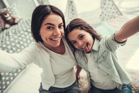 Beautiful school girl and her mom are hugging, looking at camera and smiling while playing in girls room at home