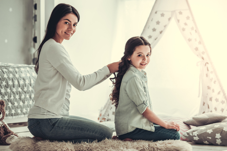 Beautiful young mom is making her cute daughter braids. Both are looking at camera and smiling while sitting in girls room at home Reklamní fotografie
