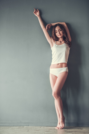 Full length portrait of beautiful young girl in white underwear posing at camera, on gray background