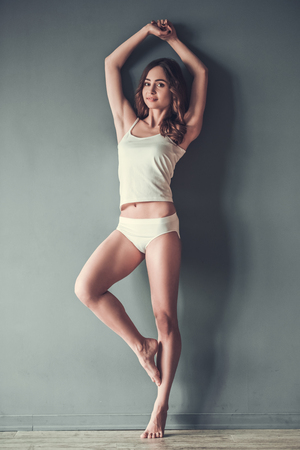 Full length portrait of beautiful young girl in white underwear posing at camera, on gray background Banco de Imagens - 77763665