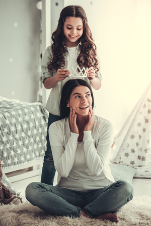 Beautiful school girl and her mom are smiling while playing with a crown in girl's room at home