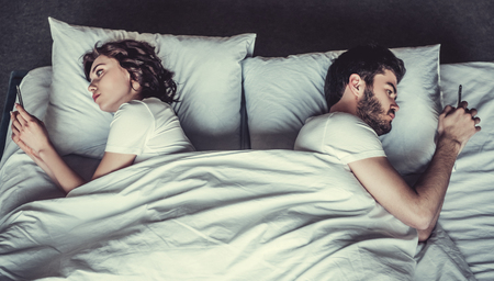 Young couple in bed using phone lying backs to each other. 스톡 콘텐츠