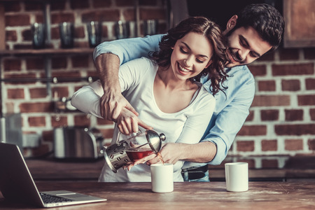 Young happy couple drinking tea and using a laptop in the kitchen at home