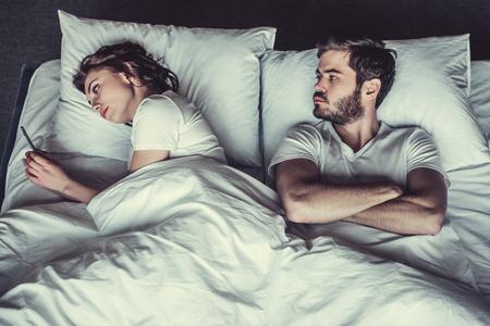 Joven hombre infeliz y su novia que utiliza el teléfono en la cama. Foto de archivo