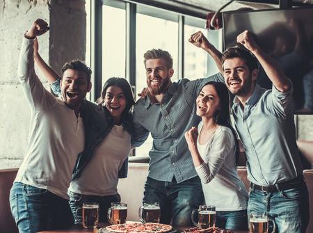 승리! TV를보고 술집에서 쉬고 그들의 팀을 응원하는 젊은 아름 다운 친구의 그룹.