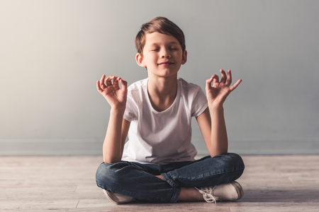 Cute little boy is meditating and smiling while sitting in lotus position on the floor Stock Photo
