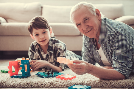 Grandpa and grandson are playing with toys, looking at camera and smiling while resting together at home