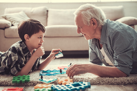 Opa en kleinzoon spelen met speelgoed, kijken elkaar aan en glimlachen terwijl ze thuis samen rusten