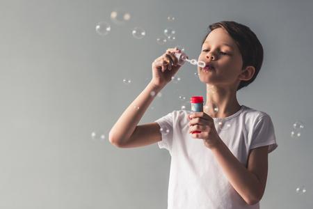Drôle petit garçon souffle des bulles de savon, sur fond gris Banque d'images - 78435002
