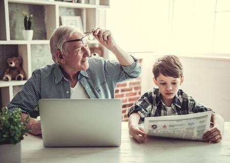 Abuelo y nieto descansando en el país. Apuesto hombre mayor está usando un ordenador portátil mientras su hijo está leyendo un periódico