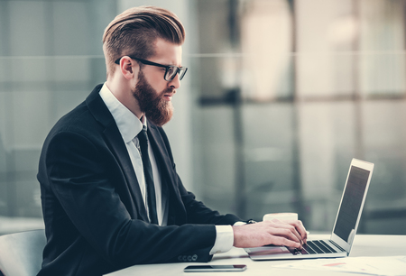 Handsome bearded businessman in classic suit and eyeglasses is using a laptop while working outdoors