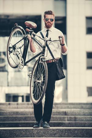 bajando escaleras: Hermoso hombre de negocios barbudo en traje clásico y gafas de sol está llevando su bicicleta y sonriendo mientras baja las escaleras