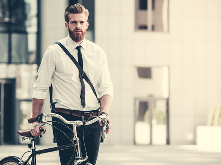 Handsome bearded businessman in classic suit is riding bicycle in city Stock Photo