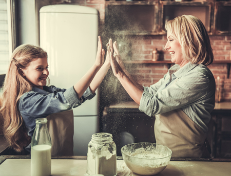 Beautiful grandma and granddaughter are clapping hands and smiling while baking in kitchen