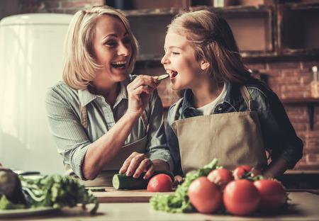Mooie oma en kleindochter zijn het proeven van komkommer en glimlachen terwijl het voorbereiden van salade in de keuken
