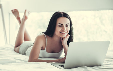 one sheet: Beautiful girl is using a laptop and smiling while lying on bed at home Stock Photo