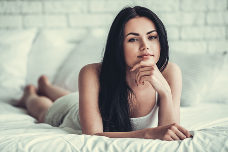 one sheet: Beautiful girl is looking at camera with tender smile while lying on bed at home